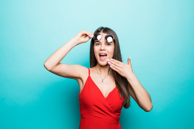 Shocked beautiful young woman in red mini dress and sunglasses cover mouth with hand on blue wall.