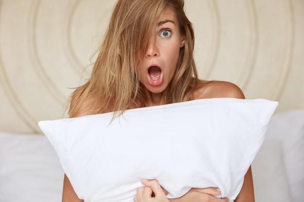 Bella giovane donna scioccata con gli occhi infastiditi e la bocca ampiamente aperta, nasconde il corpo nudo con un cuscino bianco, non si aspetta di vedere uno sconosciuto nella camera d'albergo. la reazione del silenzio e la sorpresa conncept.