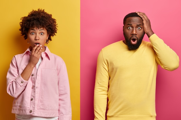 Shocked black female and male stare at camera, expresses great surprisement, open mouthes, hear unbelievable news, wear pastel pink and yellow clothes