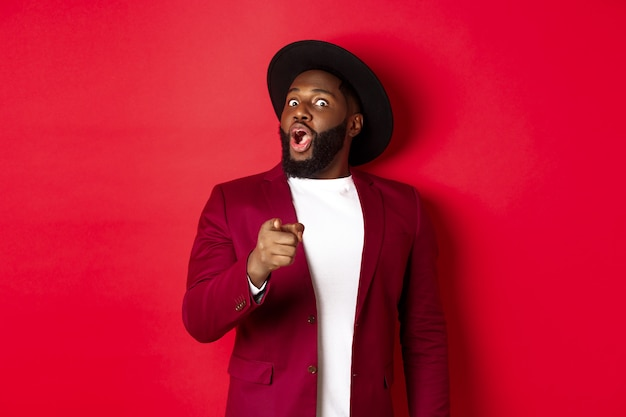 Shocked black man gasping amazed and pointing finger at camera, recognize someone, standing in red blazer and hat against studio background.