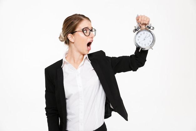 Shocked blonde business woman in eyeglasses holding alarm clock and looking on their over white wall