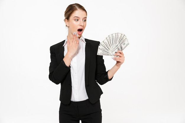 Shocked blonde business woman holding money and looking on their over white wall