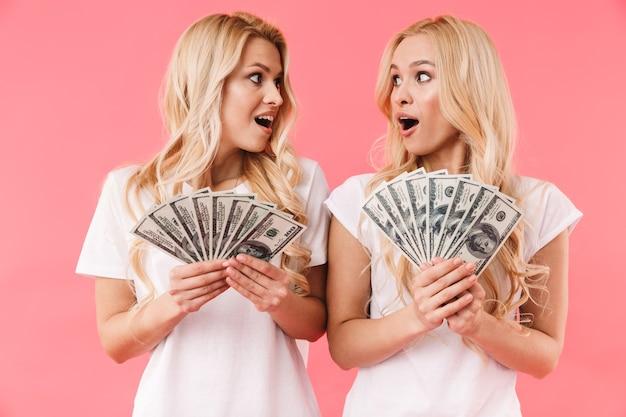 Шокированные блондинки-близнецы в футболках с деньгами, глядя друг на друга на розовой стене