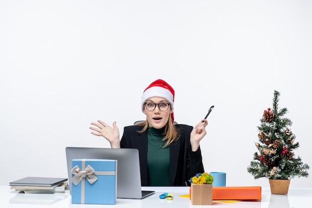 Donna bionda scioccata con un cappello di babbo natale seduto a un tavolo con un albero di natale e un regalo su di esso in ufficio su sfondo bianco