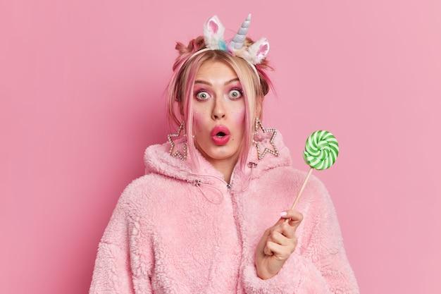 ショックを受けた金髪の若い女性がカメラのバグのある目を凝視している明るい化粧が緑のキャンディーを保持している