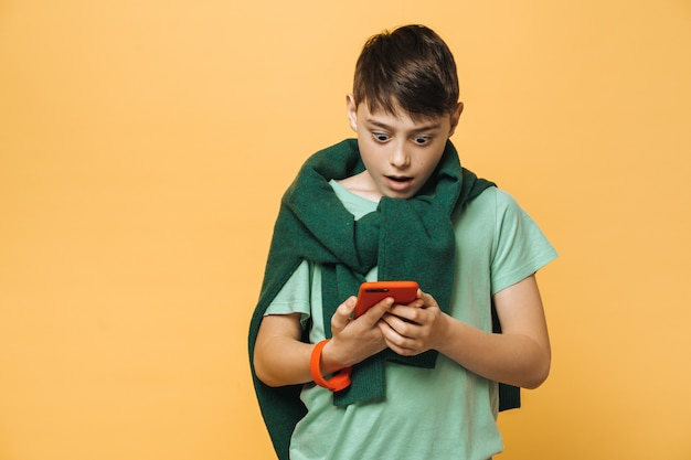 Shocked boy dressed in a green t-shirt and sweater tied up over his neck, holds his smartphone, looks at it with wide open eyes, amazed by received message. education concept.