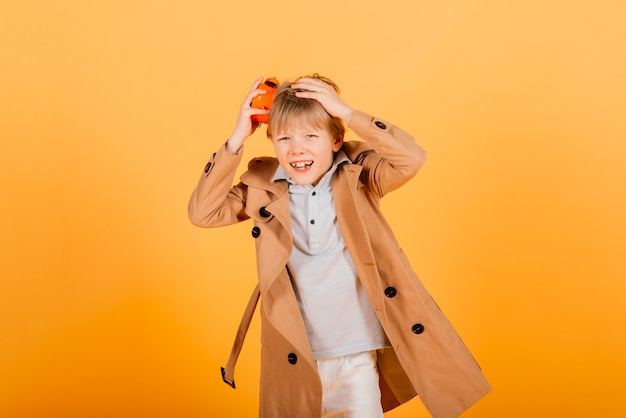 Shocked boy holding clock alarm, copy space. kid isolated over yellow background. time for school. little student overslept.