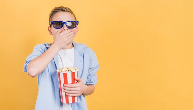 Shocked boy wearing 3d glasses holding popcorn bucket in hand standing against yellow backdrop