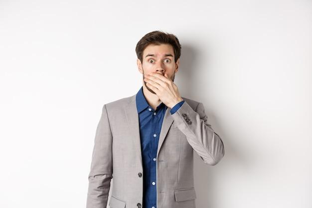 Шокированный парень в костюме, задыхаясь, прикрывая рот рукой и вытаращив глаза в камеру, поражен, стоя на белом фоне.