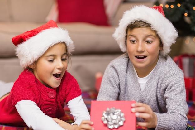 ショックを受けた兄弟姉妹が贈り物を開く