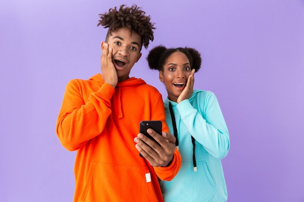 Shocked brother and sister wearing colorful sweatshirts using mobile phone, isolated over violet wall