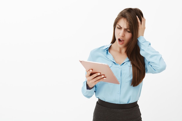 Shocked brunette businesswoman posing in the studio