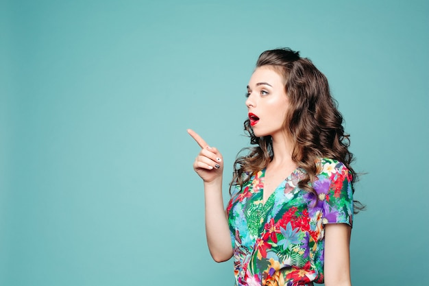 Shocked brunette girl pointing by finger at side with opened mouth.