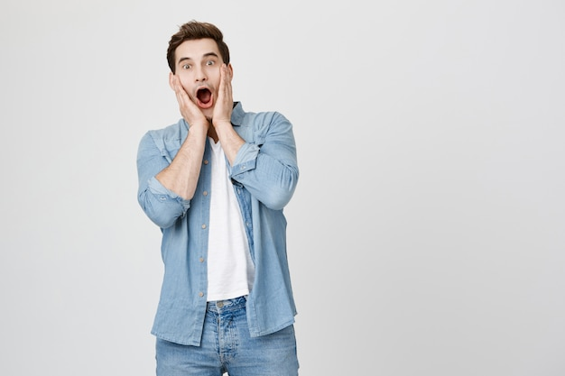 Shocked brunette guy gasping, drop jaw and scream excited