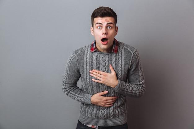 口を開けて見てセーターでショックを受けたブルネット男