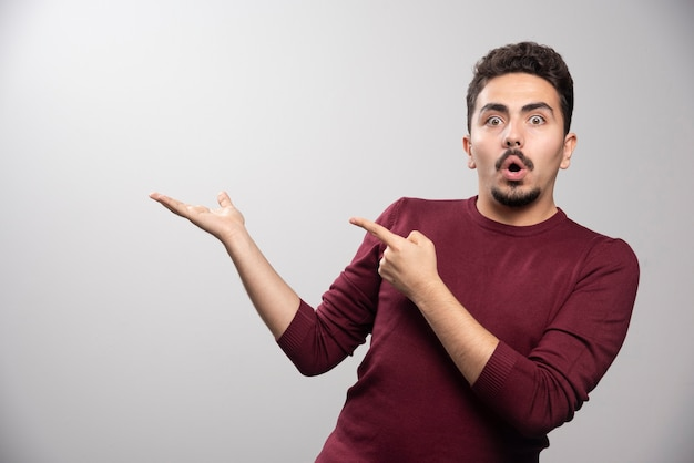 A shocked brunette man pointing at his hand .
