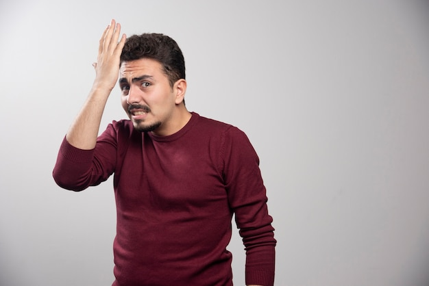 A shocked brunette man posing with his hands .