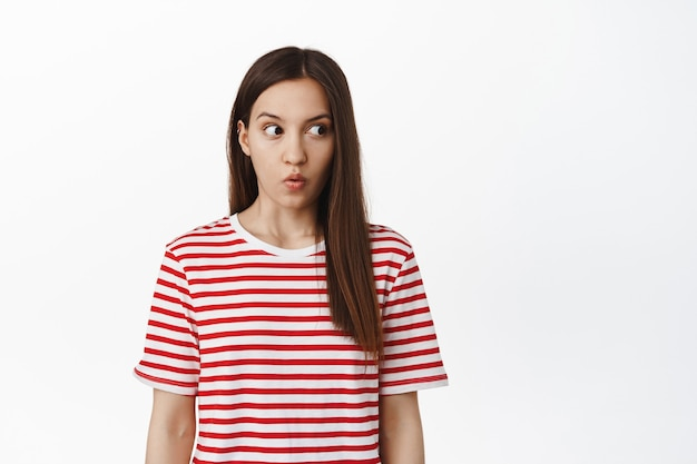 Shocked brunette woman gasping, look right at empty space with speechless startled expression, checking out smth impressive, standing against white wall.