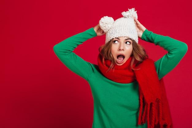 Шокированная брюнетка в свитере, смешной шапке и шарфе