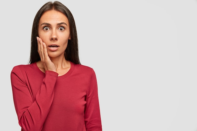 Shocked brunette woman looks with bated breath, cant believe in failure