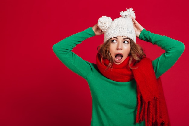 Shocked brunette woman in sweater, funny hat and scarf