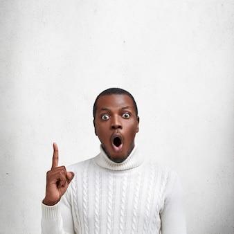 Shocked bugged eyed dark skinned man with surpsied expression, wears white sweater, indicates with fore finger upwards