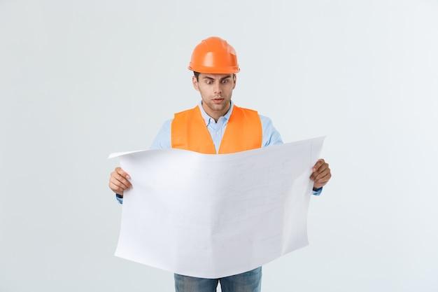ショックを受けたビルダー建設労働者は、灰色の背景に分離された計画草案を手に持っています。