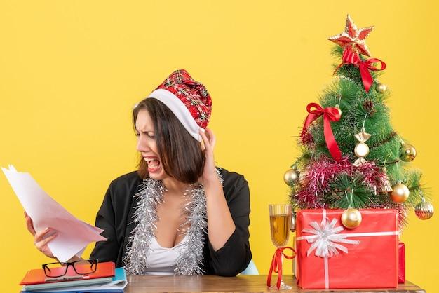 サンタクロースの帽子とドキュメントを保持し、オフィスでその上にxsmasツリーとテーブルに座って新年の装飾とスーツを着てショックを受けたビジネスレディ