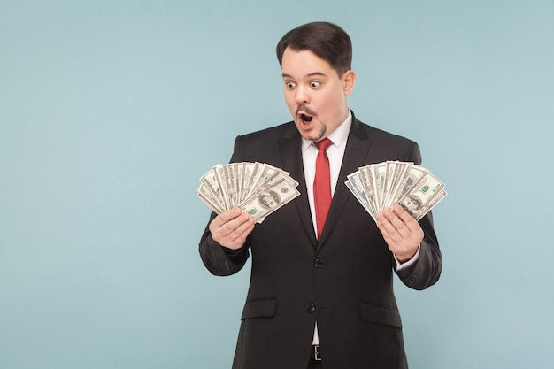 ショックを受けたビジネスマンは驚いて、多くのドルを保持しています