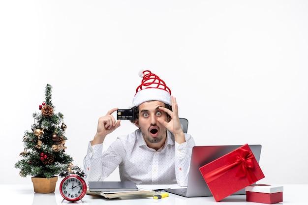 Uomo d'affari scioccato con cappello di babbo natale e tenendo la sua carta di credito guardando qualcosa con attenzione in ufficio su sfondo bianco stock photo