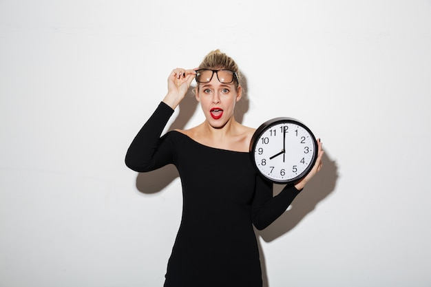 Shocked business woman holding clock.