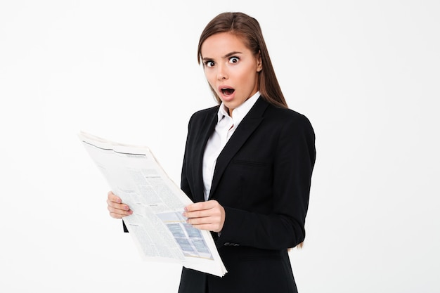 Shocked business woman holding newspaper.