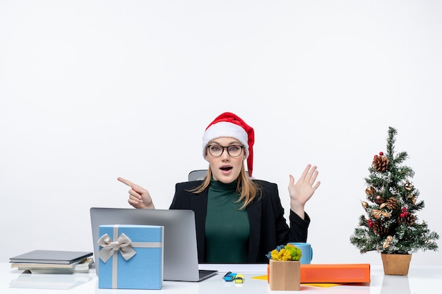 Donna d'affari scioccata con cappello di babbo natale seduto a un tavolo con un albero di natale e un regalo su di esso e concentrato su qualcosa con attenzione su sfondo bianco
