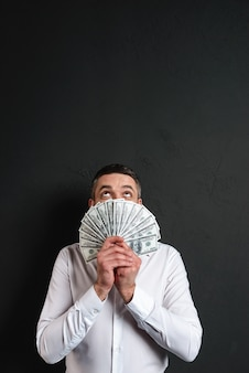 Shocked businessman covering face with money.