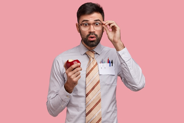 Shocked businessman dressed in formal shirt and tie, eats delicious apple, looks through spectacles in bewilderment