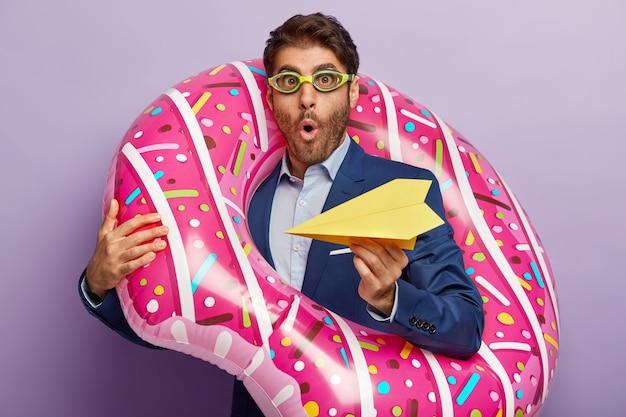 オフィスで上品なスーツでポーズをとってショックを受けたビジネスマン