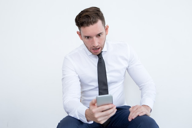 Shocked businessman reading news on phone