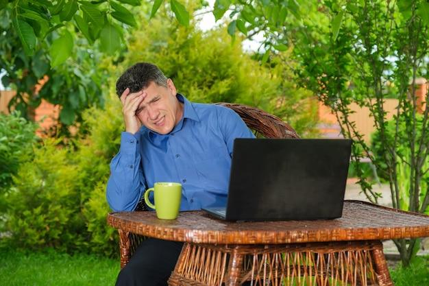 그의 뒤뜰 정원에 있는 노트북 근처에 앉아 있는 동안 가짜 뉴스로 신문을 읽는 충격을 받은 사업가. 직장에서 과도한 스트레스. 스트레스가 많은 작업 환경