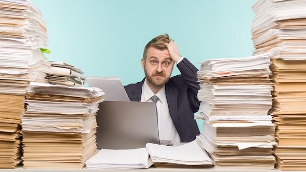 Шокированный бизнесмен сидит за столом с множеством бумаг в офисе, он перегружен работой -