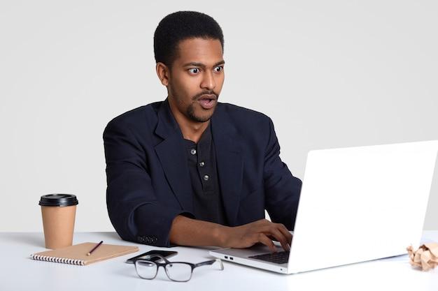 黒い肌のショックを受けたビジネスマン、キーボード情報、ラップトップコンピューターのキーボード情報、失敗したプレゼンテーションに失敗した、コーヒーを飲み、白で隔離され、メモ帳に情報を書き留める