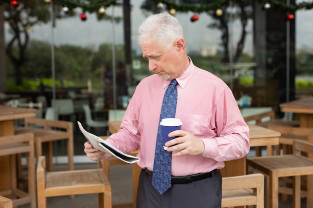 Shocked businessman with coffee cup reading newspaper