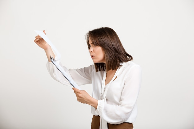 Shocked businesswoman disappointed with report
