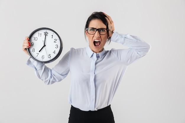 ショックを受けた実業家は、白い壁の上に孤立して立って、目覚まし時計を見せて、叫んで、スマートな服を着ています