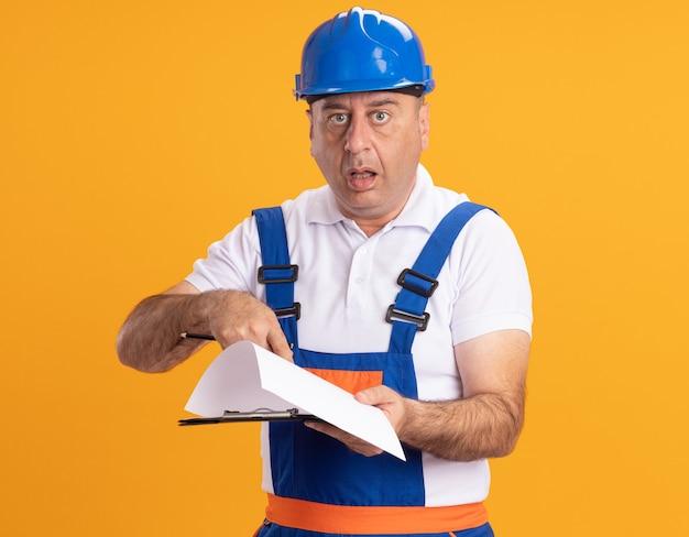 制服を着たショックを受けた白人の大人のビルダーの男は、オレンジ色のクリップボードに鉛筆とポイントを保持します