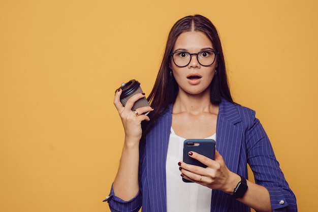 Shocked caucasian brunette  in glasses and suit holding phone in one hand and cup of coffee in another having surprised face