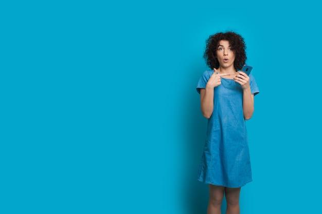 Шокированная кавказская девушка с вьющимися волосами указывает на свой мобильный телефон, позируя на синей стене с пустым пространством