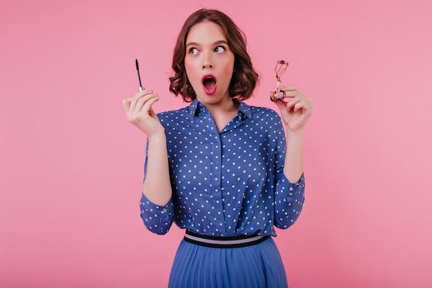 눈 화장을하는 동안 입으로 포즈를 취하는 물결 모양의 머리를 가진 충격 된 백인 여자. 유행 백인 아가씨의 실내 사진은 분홍색 벽에 그녀의 속눈썹을 컬합니다.