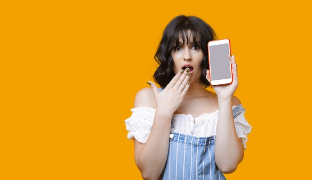 Shocked caucasian lady with black hair showing her phone while posing on a yellow wall with blank space