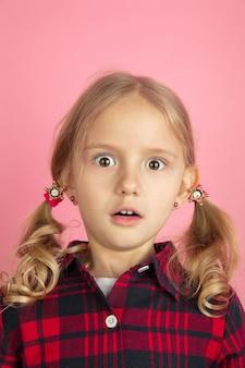 ショックを受けた。ピンクの壁に白人の少女のクローズアップの肖像画。ブロンドの髪を持つ美しい女性モデル。