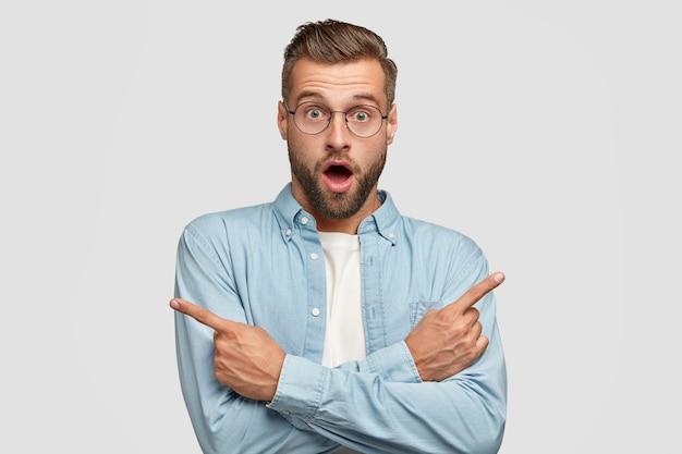 Il maschio caucasico scioccato punta su lati diversi con le dita indice, non può scegliere tra due elementi, ha un'espressione perplessa, indossa occhiali rotondi e camicia blu, isolato su un muro bianco